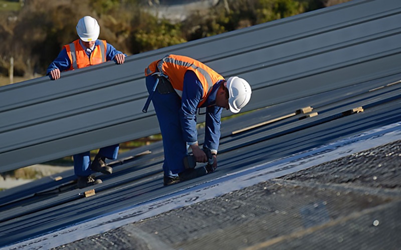 An image of 2 roofers installing a metal roof on a commercial building.