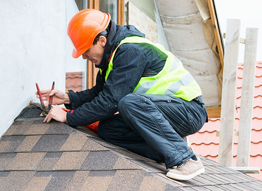 An image of a roofer working on shingles on a residential roof.