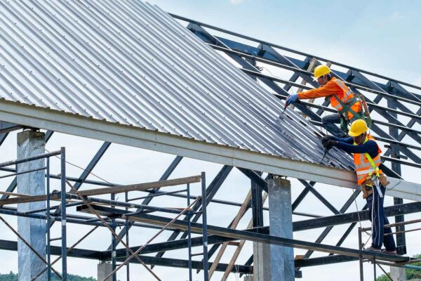 This is an image of 2 roofers working on a metal roof.